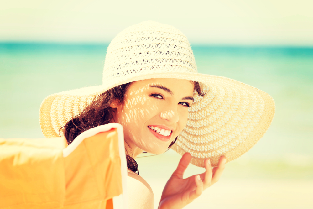 Beautiful woman in hat and swimsuit over seaside.
